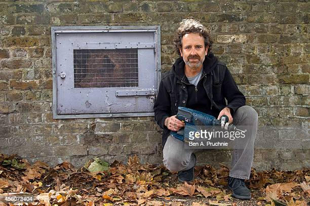 American artist Dan Witz poses after installing his new street art work 'Empty the Cages' as part of PETAs 'Animals Killed For Food' campaign on...