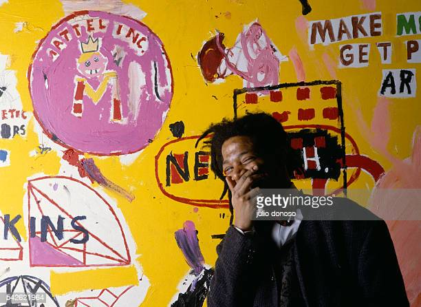 American artist musician and producer of Haitian and Puerto Rican origins JeanMichel Basquiat in front of one of his paintings during an exhibition...