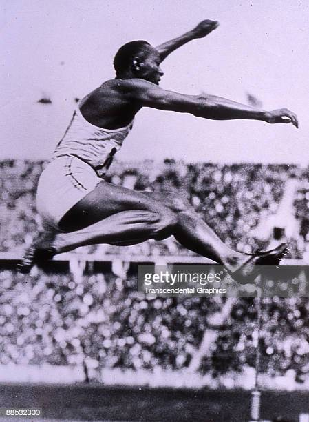American athlete and Olympic gold medal winner Jesse Owens in midair as he completes in the Long Jump at the Olympic Games Berlin Germany early...