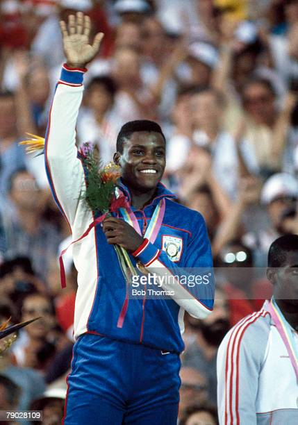American athlete Carl Lewis celebrates on the medal winners podium after being awarded the gold medal after winning the Men's 100 metres event with a...