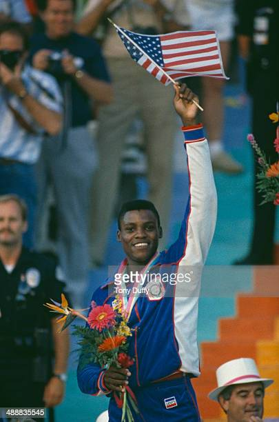 American athlete Carl Lewis waves the Stars and Stripes after being awarded a gold medal at the Los Angeles Memorial Coliseum during the Olympic...