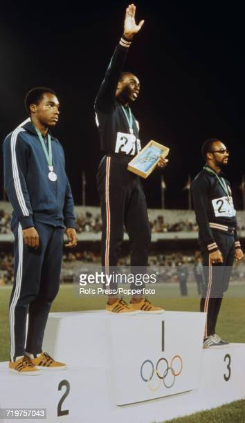 American athlete Jim Hines stands in centre and raises one arm on the podium after finishing in first place to win the gold medal in the Men's 100...