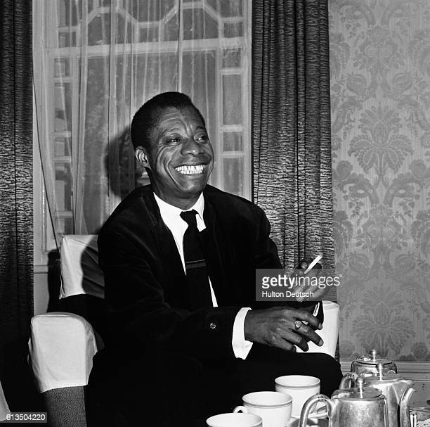 American author and civil rights activist James Baldwin listens to a reporter's question with a smile during an interview at the Whitehall Hotel in...