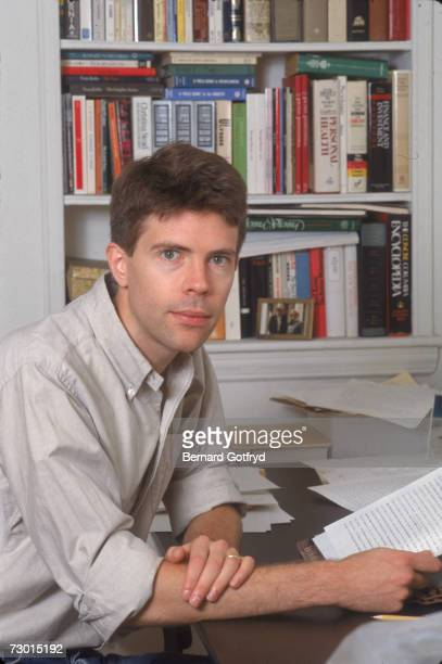 American author and college professor Jonathan Franzen sits at a table in front of a bookshelf and holds a typescript August 12 1988