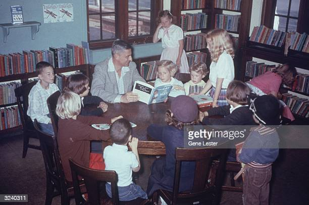 American author and illustrator Dr Seuss reading his book 'The Cat in the Hat' to a circle of children at a public library in La Jolla California...