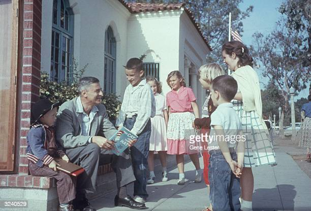 American author and illustrator Dr Seuss sits outdoors talking with a group of children holding a copy of his book 'The Cat in the Hat' La Jolla...