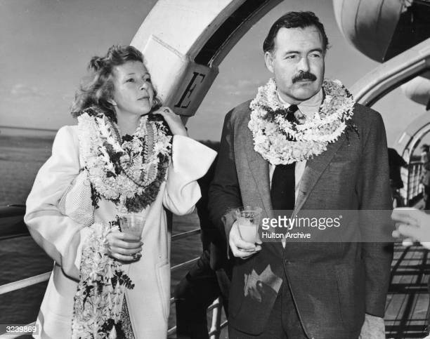 American author Ernest Hemingway and his wife journalist Martha Gellhorn stand on deck aboard a ship wearing multiple leis and holding cocktails