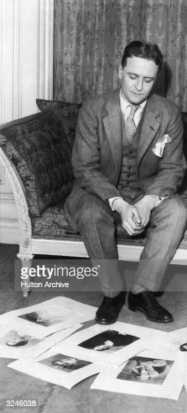 American author F Scott Fitzgerald sits on a sofa looking at photographs of his wife Zelda spread out on the floor