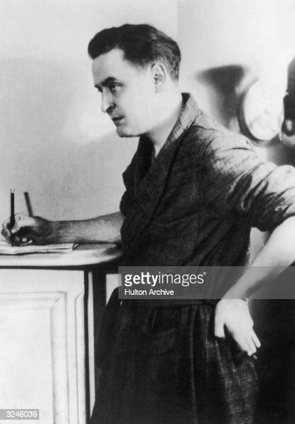 American author F Scott Fitzgerald writes in a notebook on top of a dresser wearing a bathrobe