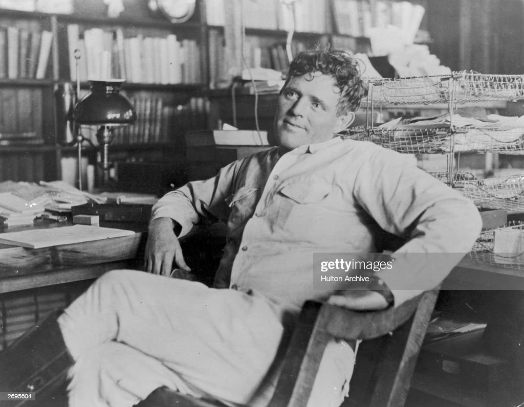 American author Jack London reclines next to his desk in a wooden chair smiling his legs crossed