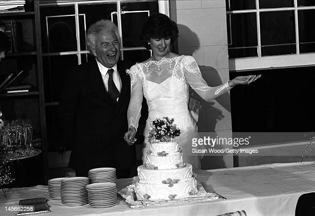 American author Joseph Heller and his bride Valerie Humphries share a laugh as they stand behind their wedding cake at their reception April 1987