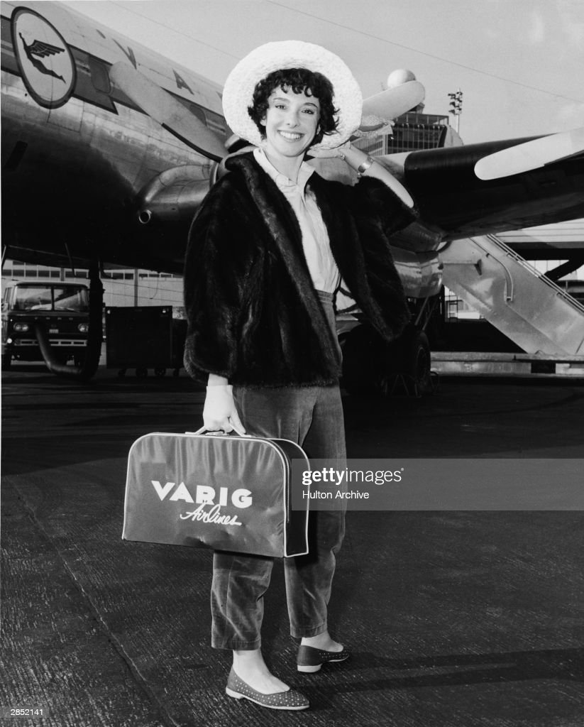 American author Rona Jaffe stands on the tarmac in front of a Varig Airlines plane at Idlewild Airport (later renamed John F. Kennedy Airport) following the completion of filming 1959's 'The Best Of Everything,' directed by Jean Negulesco, which was based on Jaffe's bestselling novel, December 6, 1959. She holds her hat with her left hand while holding a Varig Airlines carry-all in her right.