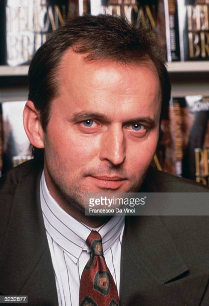 American author screenwriter and former criminal defense lawyer John Grisham posing in front of a bookcase