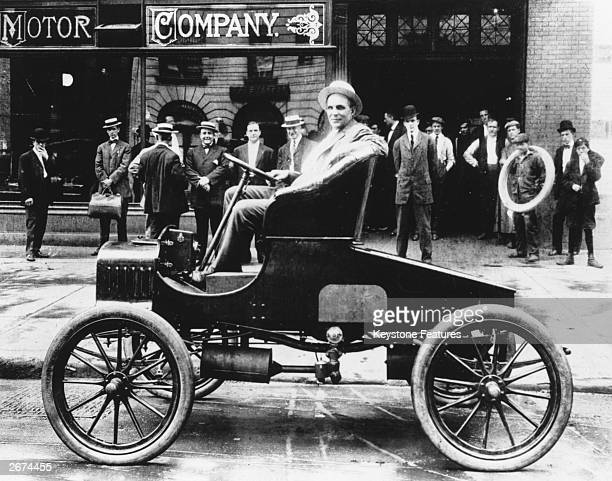 American automobile engineer and manufacturer Henry Ford poses in the driver's seat of his latest model outside the Ford factory in Detroit Michigan