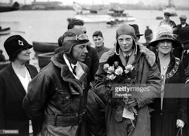 American aviator Amelia Earhart holds a bouquet of flowers upon her arrival at Southampton after piloting her aeroplane Friendship from Burry Port...