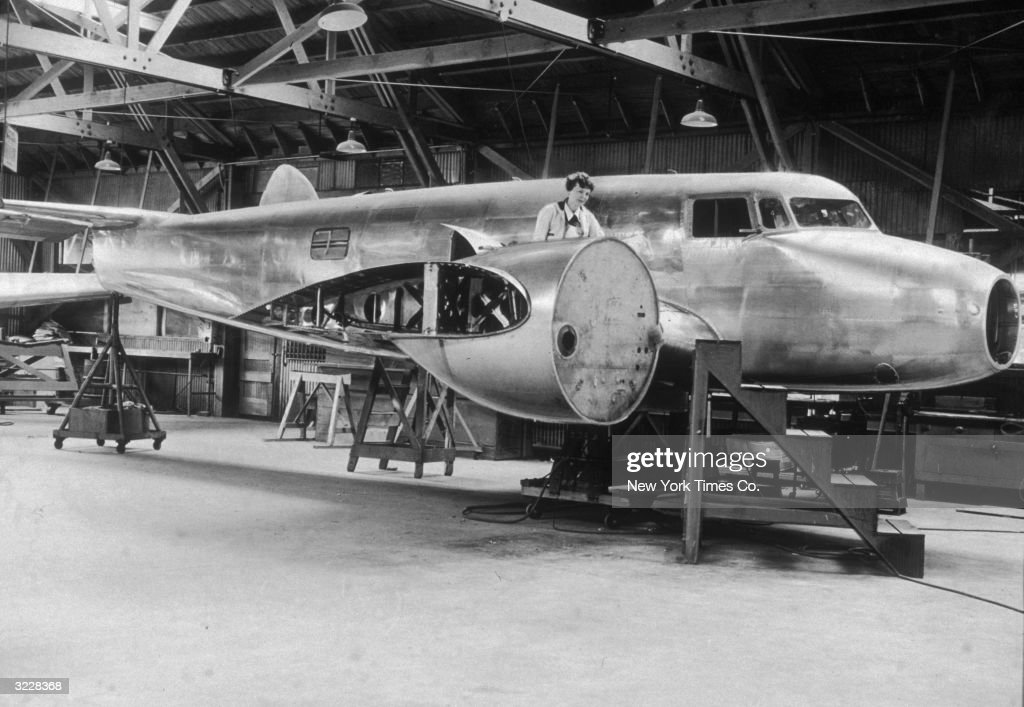American aviator Amelia Earhart (1898 - 1937) inspects her uncompleted Lockheed Electra airplane inside a hangar at Purdue University, Indianapolis, Indiana.