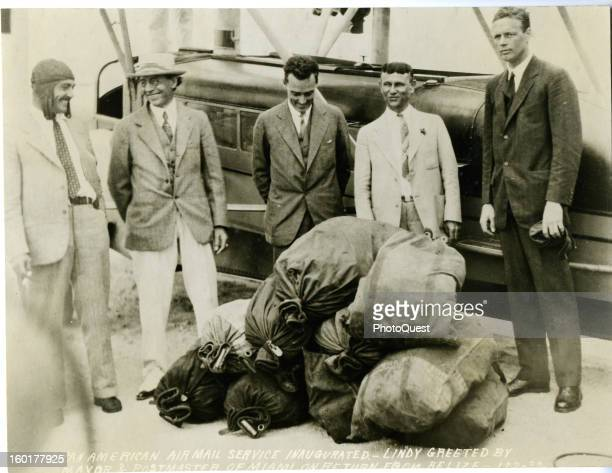 American aviator Charles A Lindbergh poses with the mayor and postmaster with bags of mail in front of a Sikorsky S40 'flying boat' used on the...