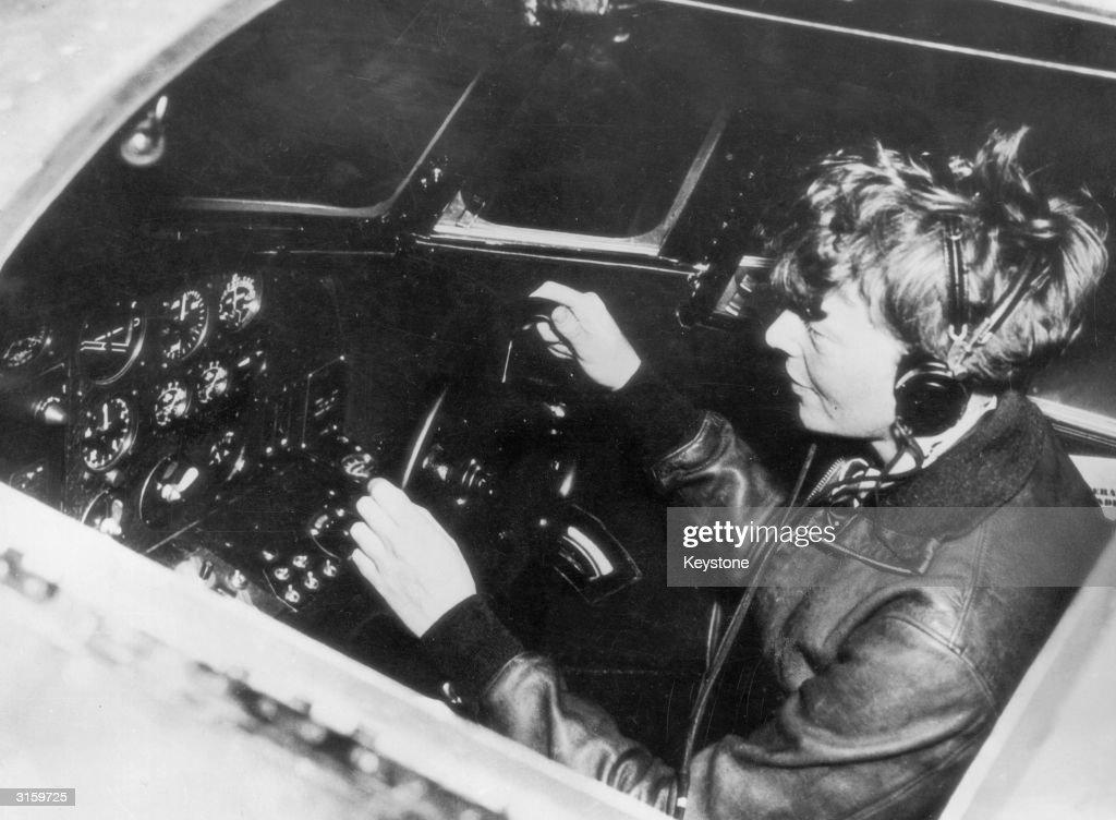 American aviatrix Amelia Earhart (1897 - 1937) operates the controls of a flying laboratory, circa 1935.
