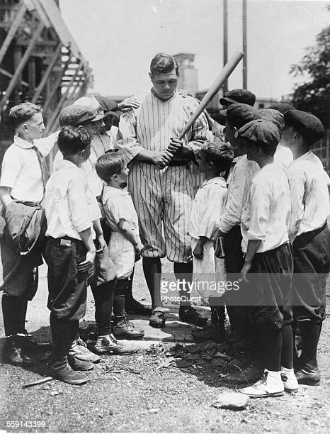 American baseball player Babe Ruth demonstrates proper grip to to a group of boys at the Polo Grounds New York New York late 1910s or early 1920s