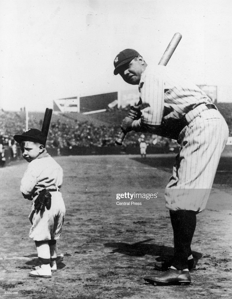 American baseball player Babe Ruth playing baseball in a full stadium with a small child