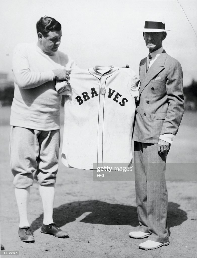 American baseball player Babe Ruth poses with an unidentified man as he holds up his new uniform as a member of the Boston Braves at the Braves'...