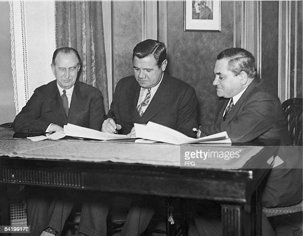 American baseball player Babe Ruth signs a contract to join the Boston Braves team while he is watched by Charles F Adams and Emil Fuchs the team's...