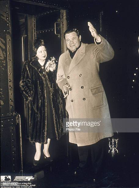 American baseball player George Herman 'Babe' Ruth dressed in an overcoat holds a cigar and waves as his wife Claire Merritt Hodgson in a fur coat...