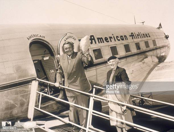 American baseball player George Herman 'Babe' Ruth waves his hat as his wife Claire Merritt Hodgson smikes beside him on the gangwy of an American...