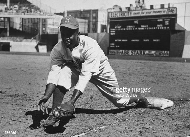American baseball player Jackie Robinson grounds a ball at first place while warming up for an exhibition game against the New York Yankees Ebbets...