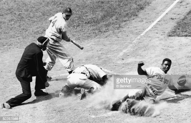 American baseball player Jackie Robinson of the Brooklyn Dodgers is tagged out by Cubs catcher Rube Walker after attempting to slide in and steal...
