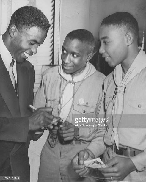 American baseball player Jackie Robinson of the Brooklyn Dodgers signs autographs for Boy Scouts Philadelphia Pennsylvania November 15 1947