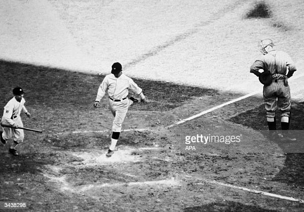 American baseball player Stanley 'Bucky' Harris playing for the Washington Senators lands on home plate after scoring a homerun during the seventh...