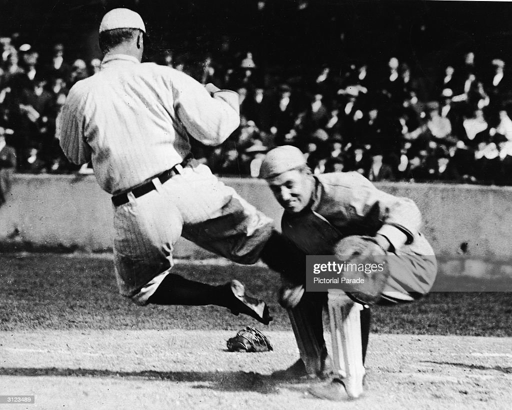American baseball player Ty Cobb (1886 - 1961) takes a high slide into the knees of the opposing team's catcher during a game for the Detroit Tigers, 1920s.