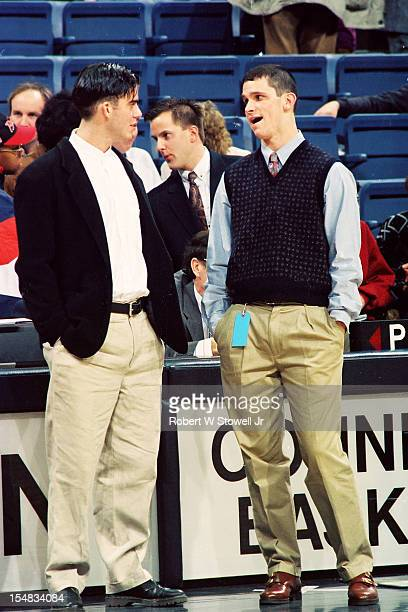 American basketball player Jeff Calhoun of the University of Connecticut listens to player Danny Hurley of Seton Hall as they both stand courtside...