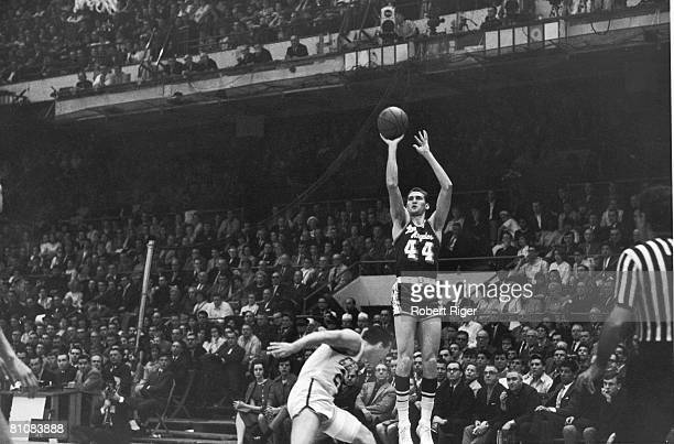 American basketball player Jerry West of the Los Angeles Lakers leaps into the air to make a shot during a game against the Boston Celtics 1960s or...