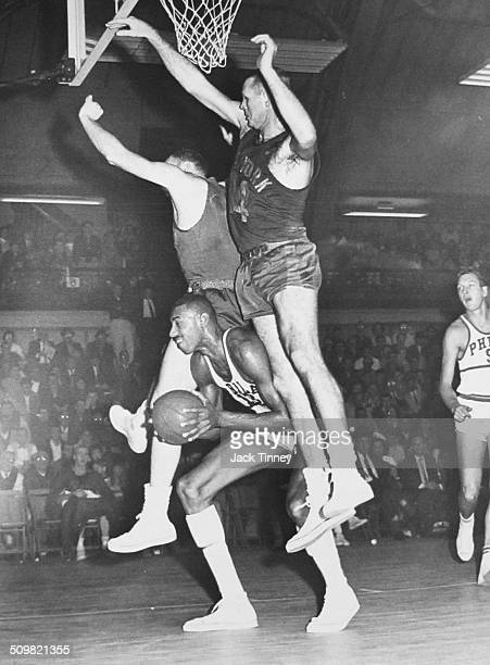 American basketball player Wilt Chamberlain of the Philadelphia Warriors with the ball as he is blocked by two New York Knicks players during a game...