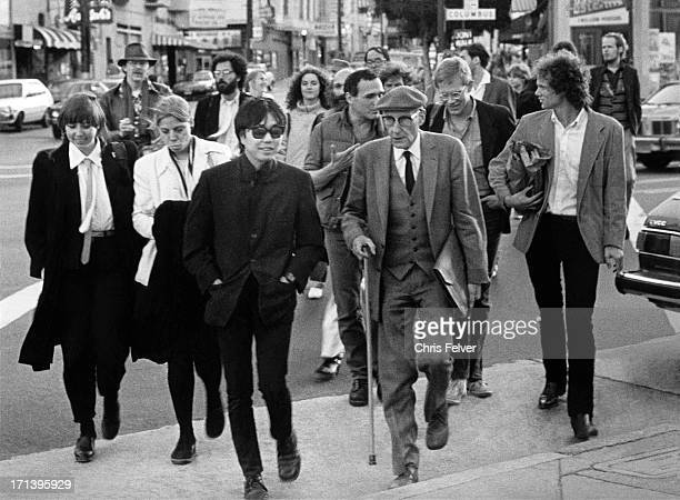 American Beat author William S Burroughs surrounded by unidentified others walks across Columbus Avenue San Francisco California 1981