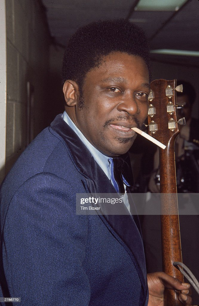 American blues guitarist B.B. King stands holding a guitar with a cigarette in his mouth, circa 1970.