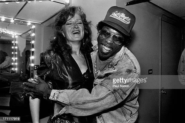 American blues musicians Bonnie Raitt and Buddy Guy share a laugh as they embrace backstage at the Vic Theater Chicago Illinois May 12 1989