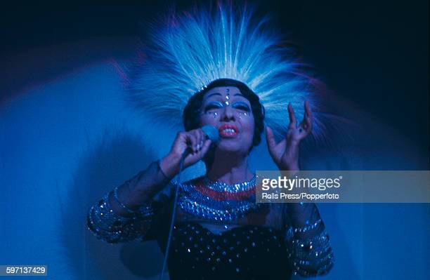 American born French singer and dancer Josephine Baker performs on stage wearing an ornate feather headdress at a cabaret nightclub in Paris France...