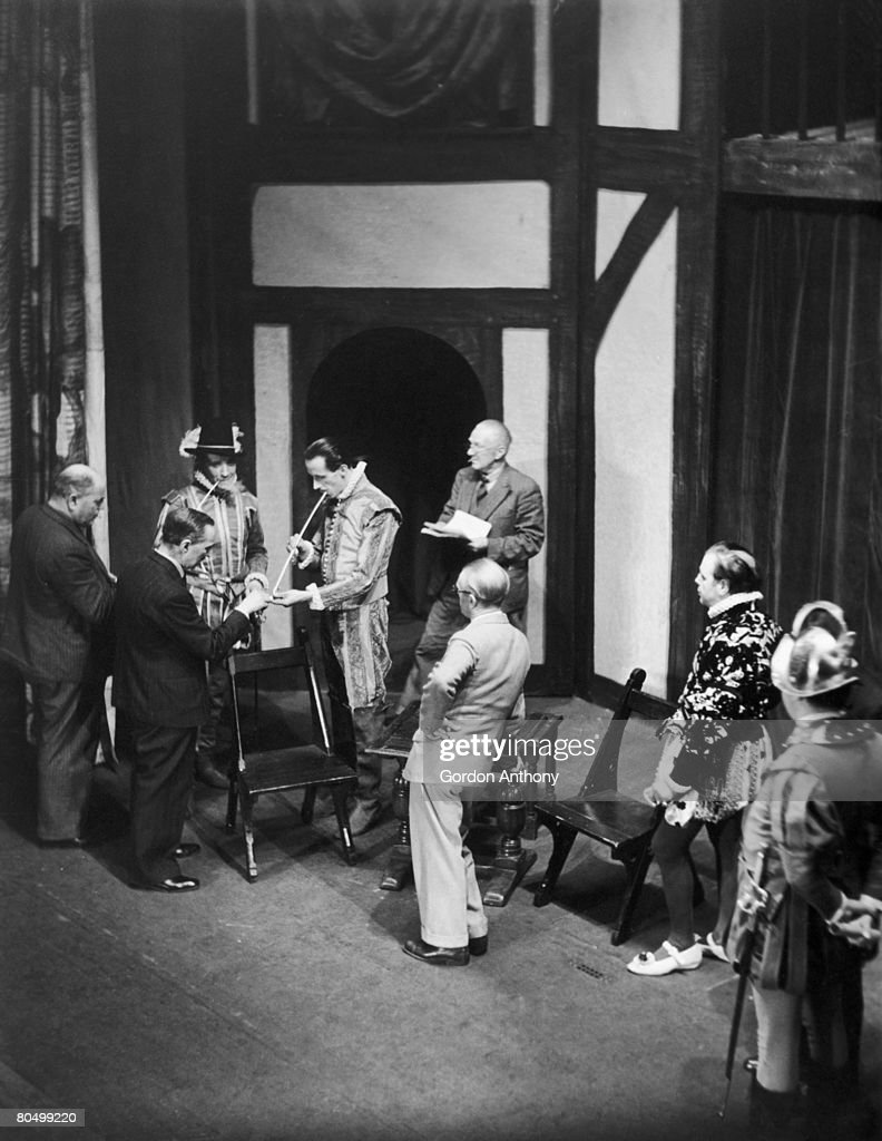 American born Shakespearean actor Ernest Milton (1890 - 1974, third from left) and actor/director Robert Atkins (far left) during a break from rehearsals of a production of 'All's Well That Ends Well' at the Vaudeville Theatre, London, 1940.