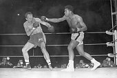 American boxer and world heavyweight champion Muhammad Ali throws a long right to British challenger Henry Cooper's injured left eye in the sixth...