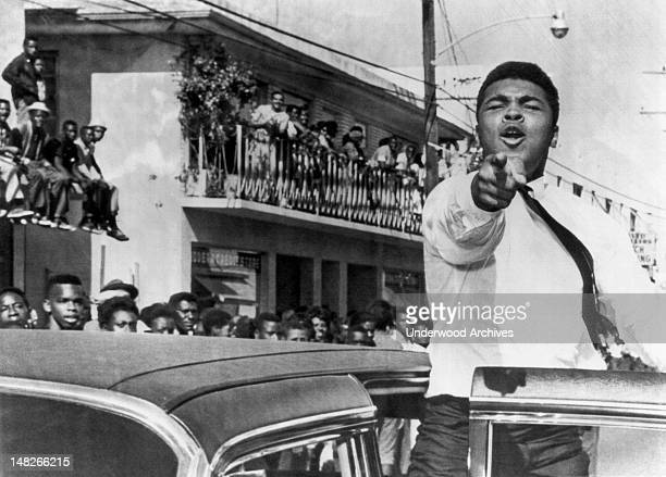 American boxer Cassius Clay points at the camera from an open car door as he takes part in a prefootball game parade Miami Florida December 14 1963...