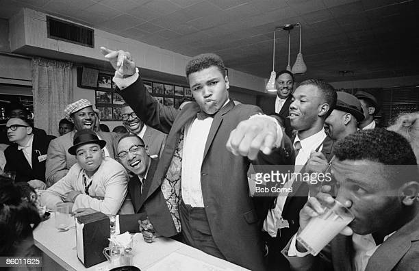 American boxer Classius Clay dressed in a tuxedo holds court at a diner with fans friends and admirers after his defeat of Sonny Liston Miami Florida...