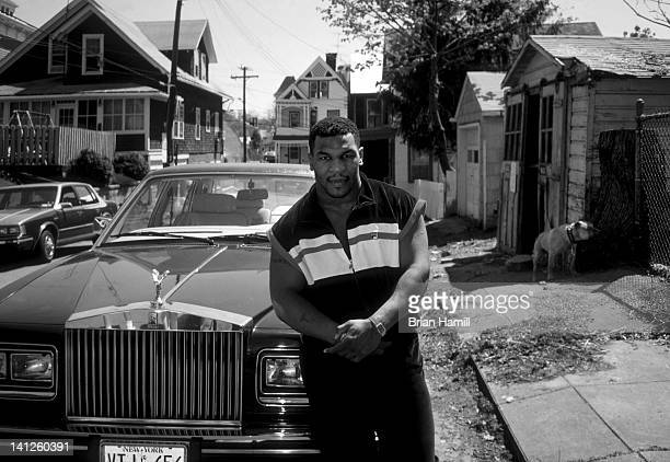 American boxer Mike Tyson poses in front of a Rolls Royce parked on a side street Catskill New York April 1987