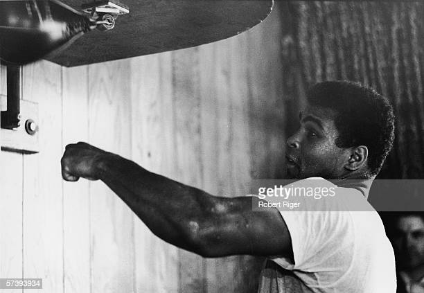 American boxer Muhammad Ali dressed in a tshirt trains with a speed bag early 1960s