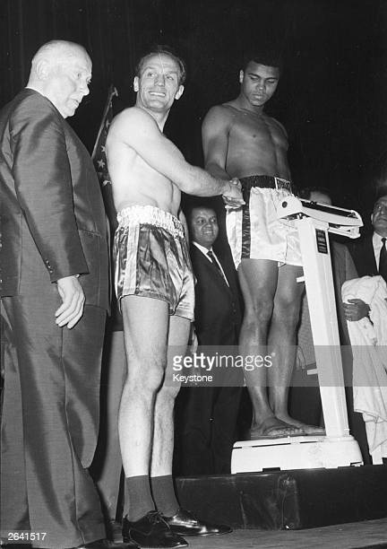 American boxer Muhammad Ali the world heavyweight champion shakes hands with British boxer Henry Cooper at the weighin at the Odeon Leicester Square...