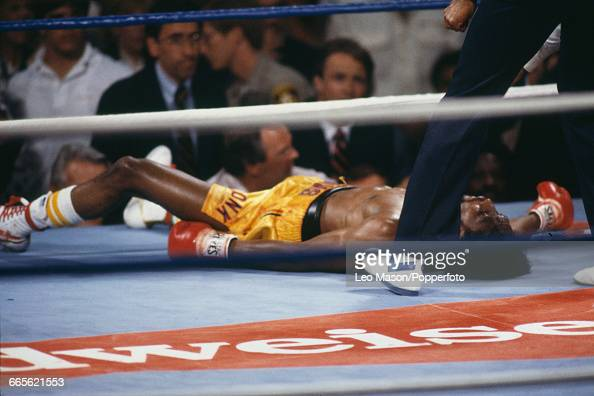 American boxer Thomas Hearns in yellow shorts lies on the canvas after being knocked out by Marvelous Marvin Hagler in the third round of the fight...