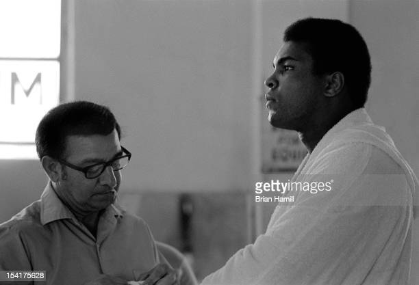 American boxing coach Angelo Dundee tapes the hand of heavyweight boxer Muhammad Ali during training at the 5th Street Gym Miami Florida 1971 Ali was...
