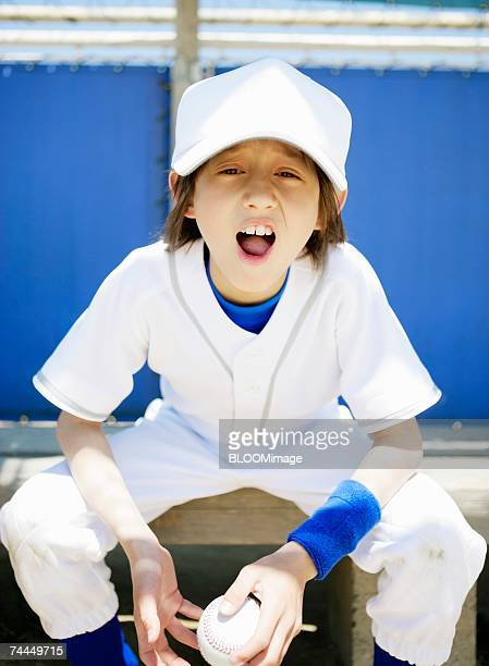 American boy wearing uniform of baseball looking at camera with sitting on bench ,portrait